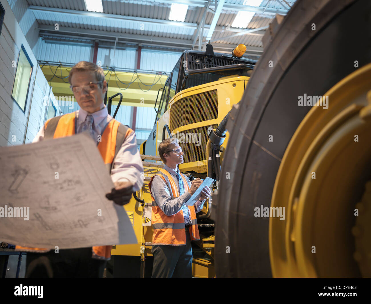Engineers with engineering drawings inspecting heavy truck - Stock Image