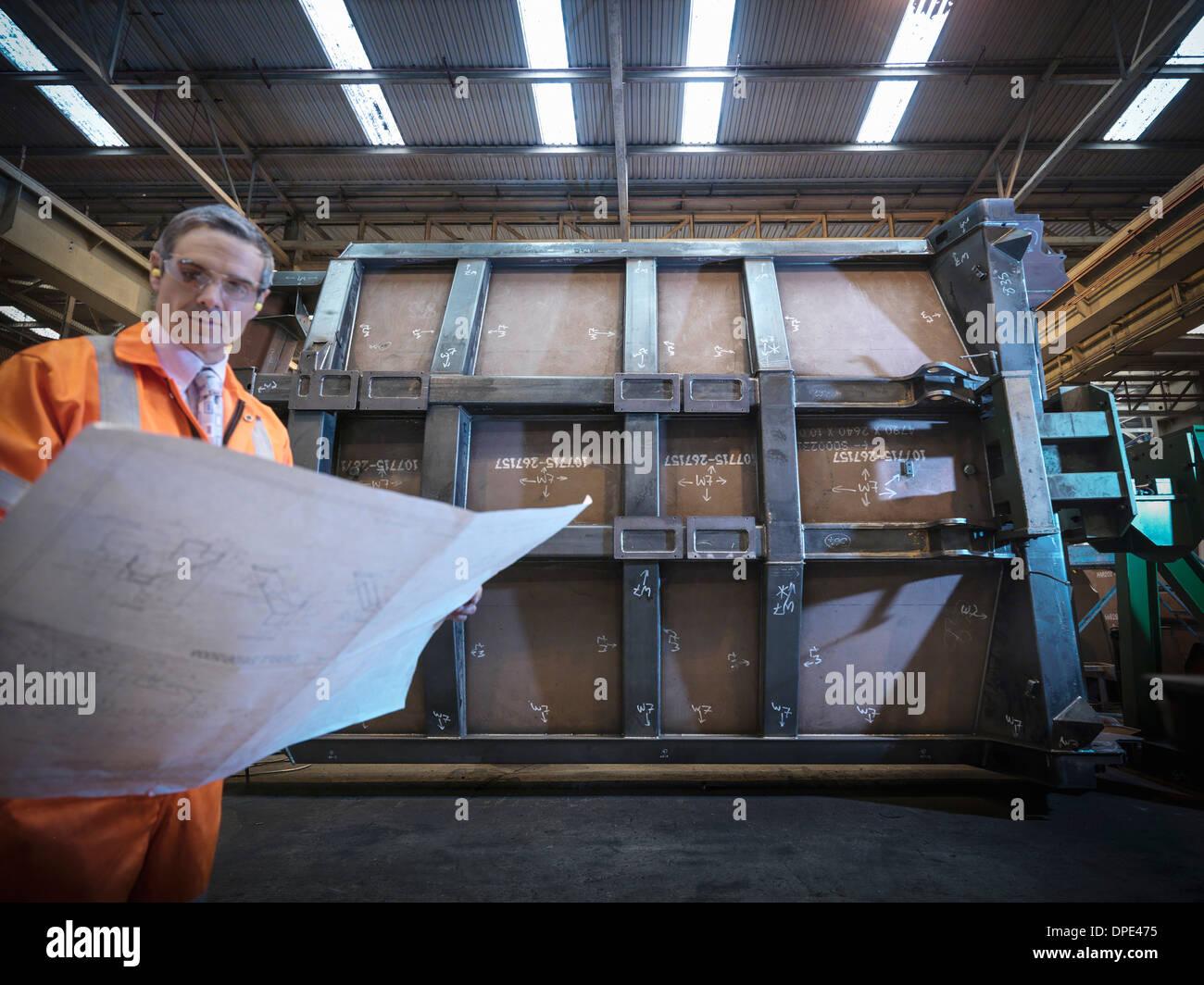 Engineer inspecting engineering drawings in factory - Stock Image
