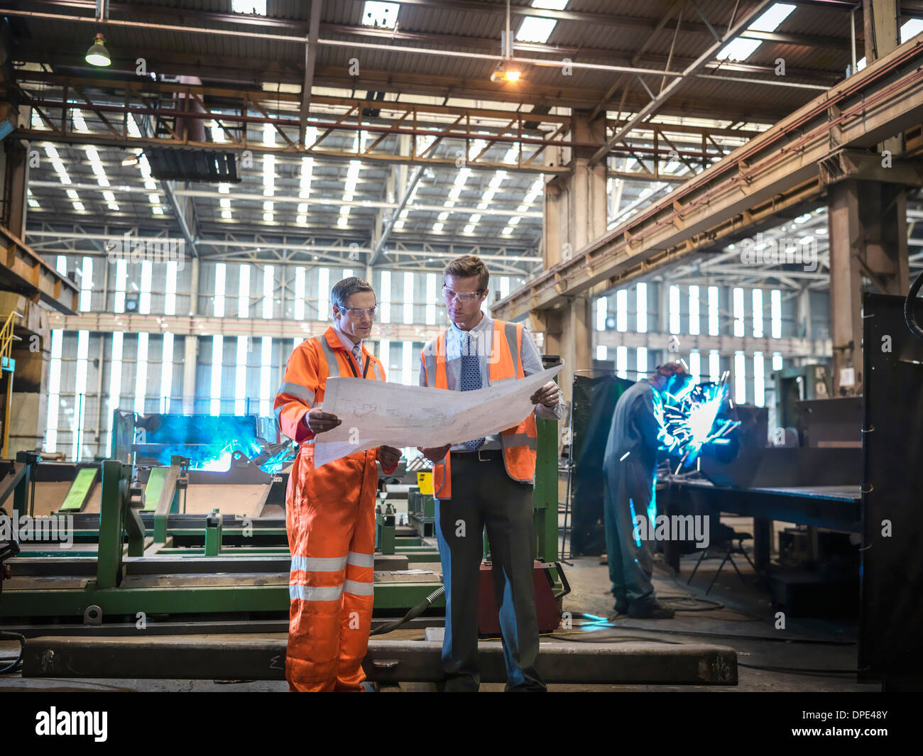 Engineers inspecting engineering drawings in factory - Stock Image