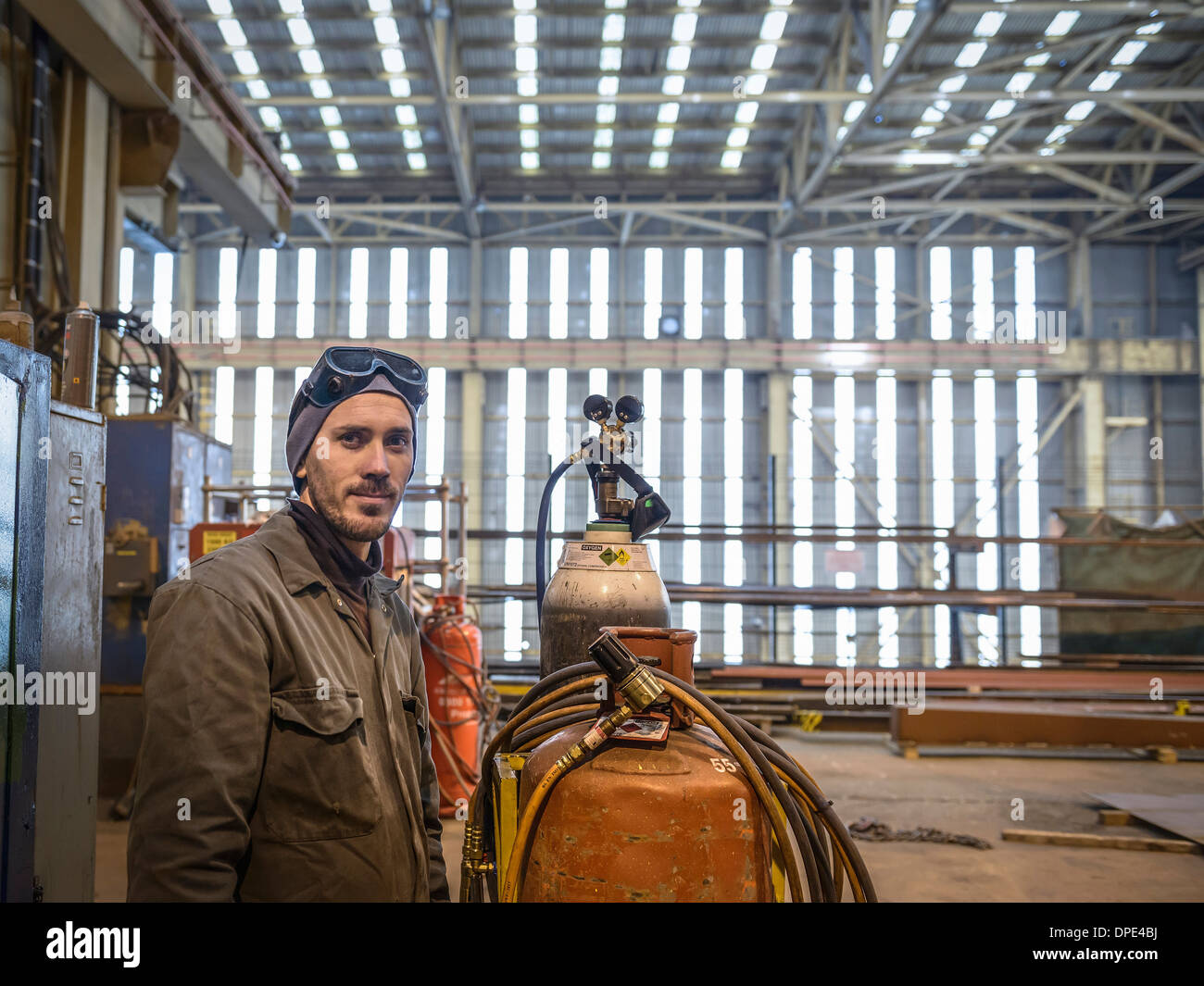 2f40702ad6c Portrait of welder wearing overalls and safety goggles in factory - Stock  Image
