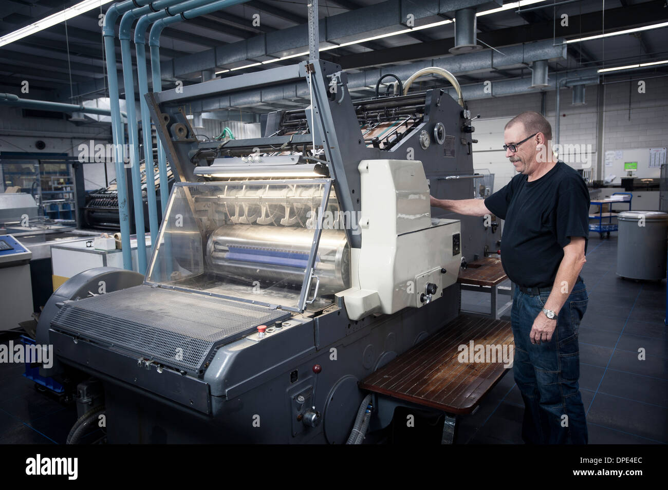 Worker operating print machine in printing workshop - Stock Image