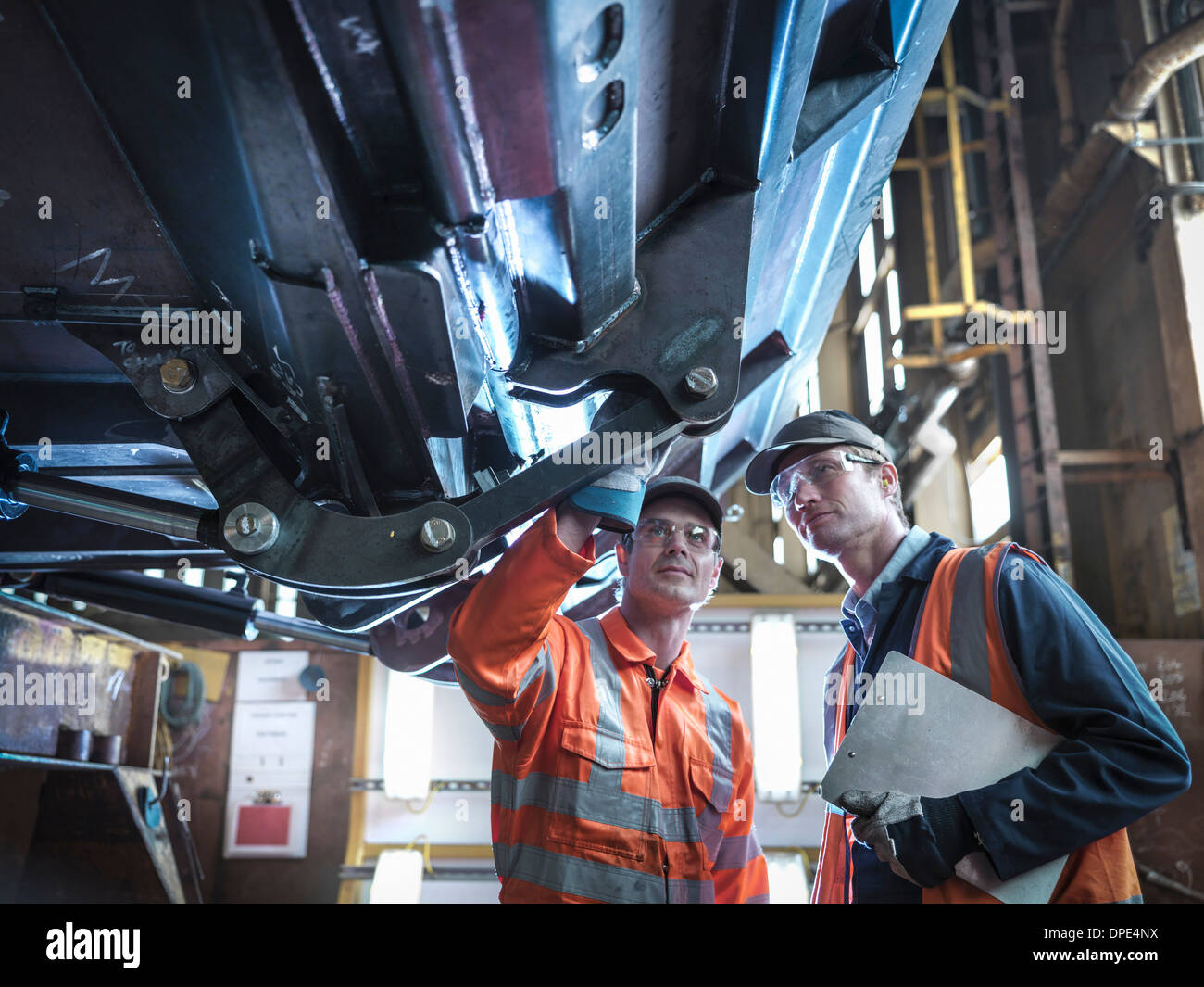 Engineers inspecting work in factory - Stock Image