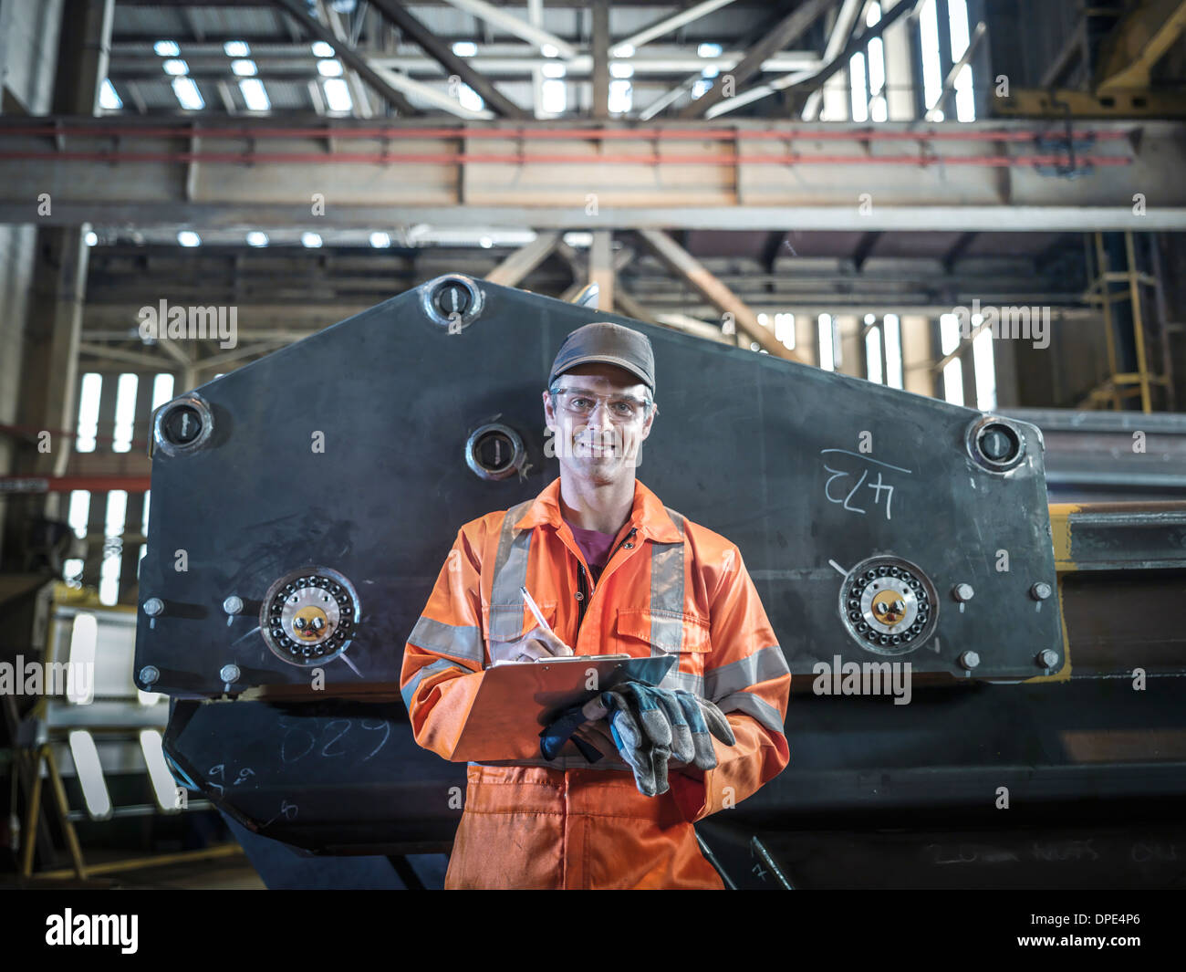 Portrait of engineer holding clipboard in factory - Stock Image