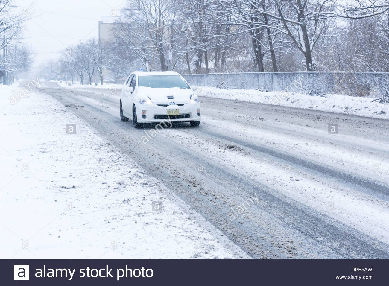 Car on day so cold that salt ineffective in melting snow creating a slippery slush on road in Toronto Ontario Canada - Stock Image