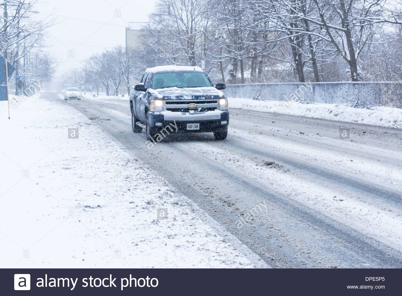 Truck on day so cold that salt ineffective in melting snow creating a slippery slush on road in Toronto Ontario Canada - Stock Image