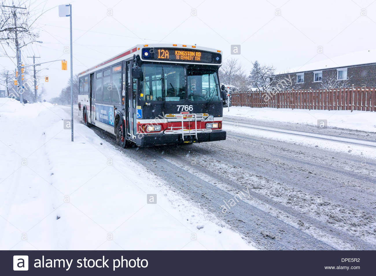 City bus on day so cold that salt ineffective in melting snow creating a slippery slush on road in Toronto Ontario Canada - Stock Image