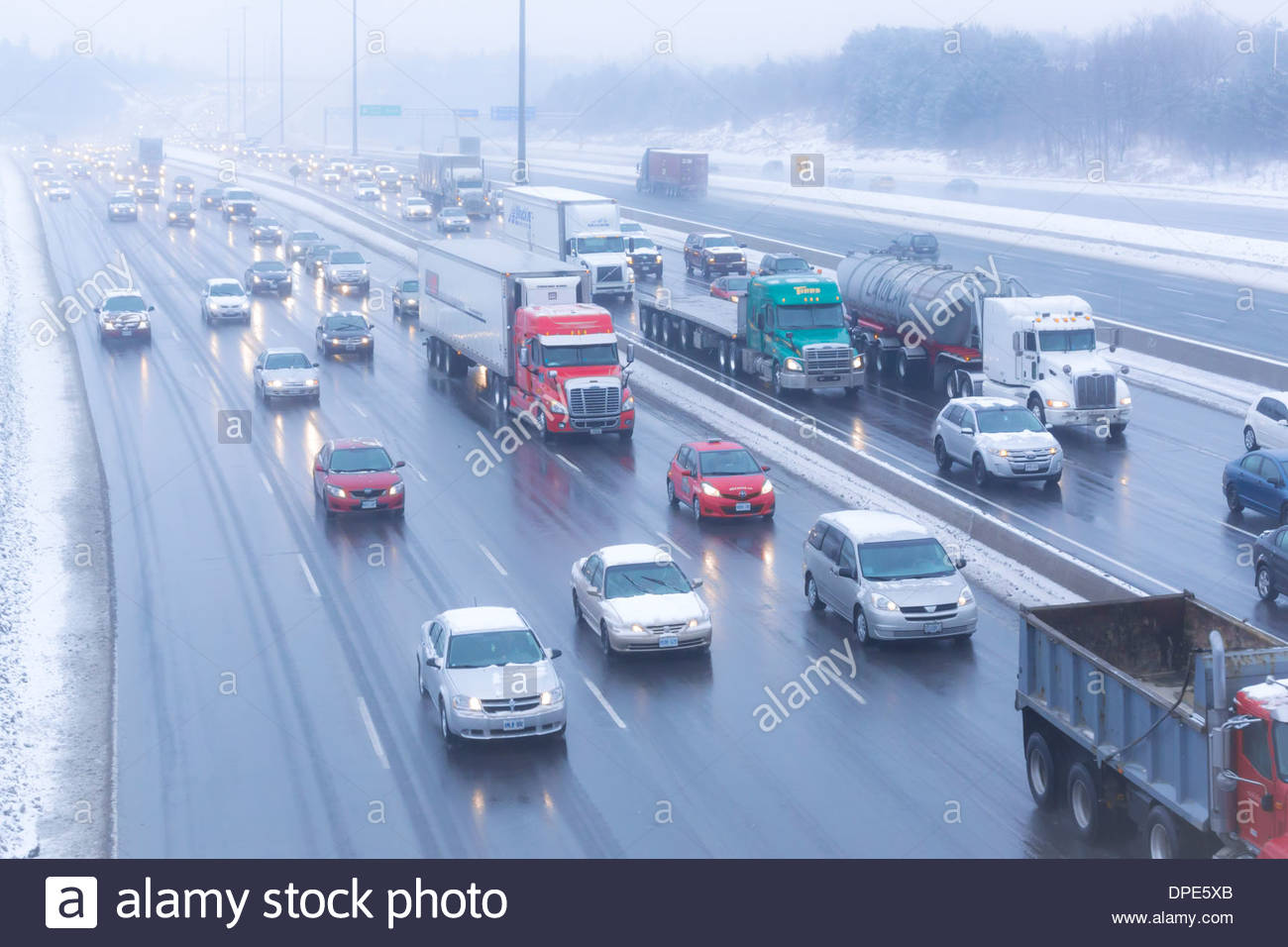Highway 401 morning inbound commuter traffic jammed up due to freezing rain storm in winter in Toronto Ontario Canada - Stock Image