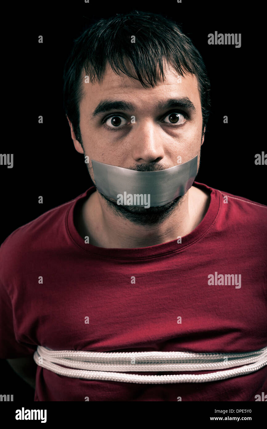 Kidnapped man hostage with tape over mouth and tied up with rope - Stock Image