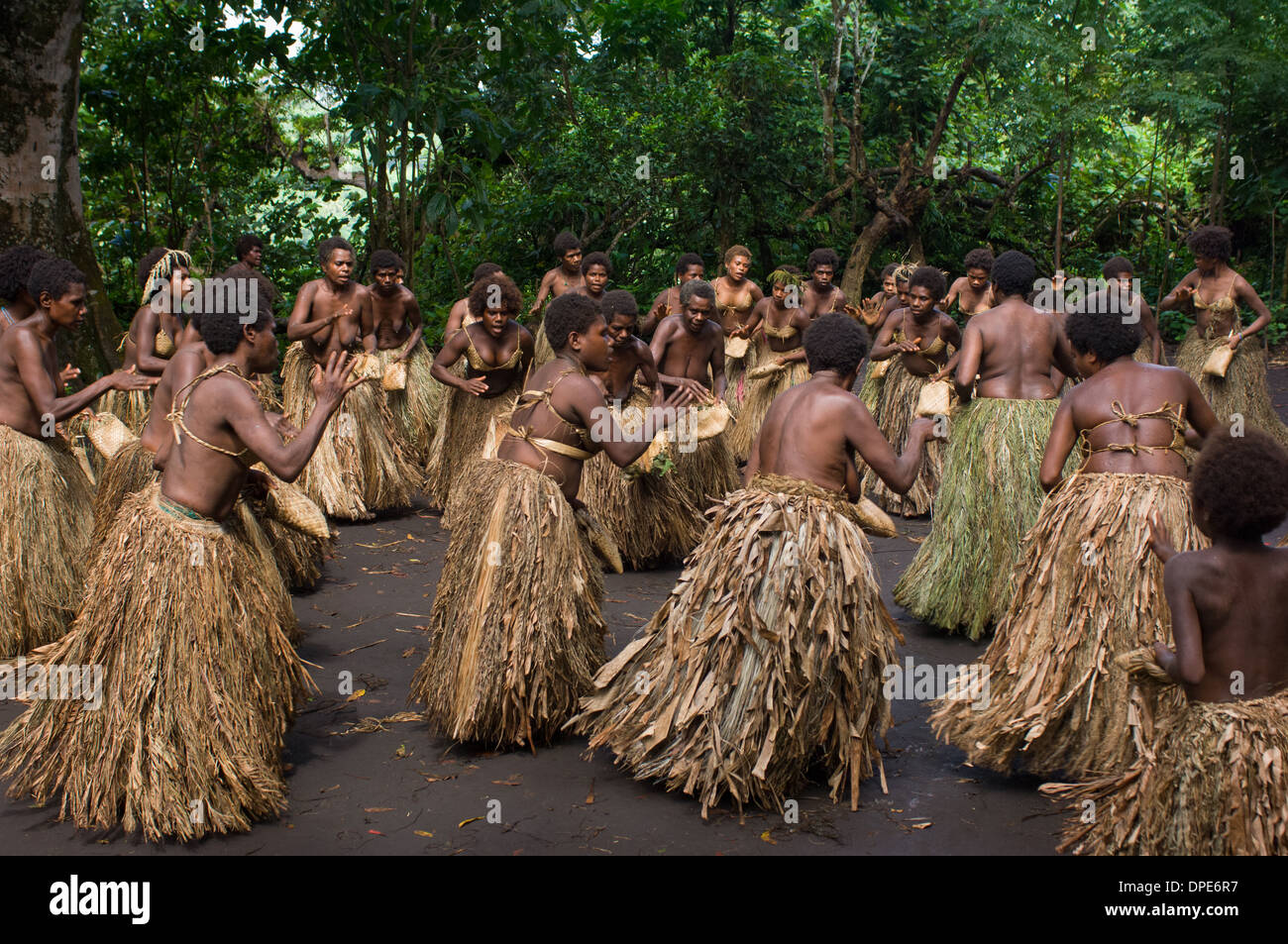 Women in grass skirts, performing Kastom (traditional culture) dancing at Yakul Village, Tanna Island, Vanuatu - Stock Image