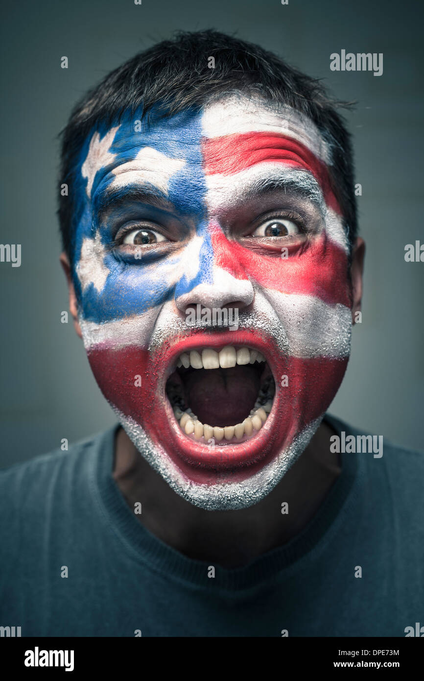 Portrait of angry man with USA flag painted on face. Stock Photo