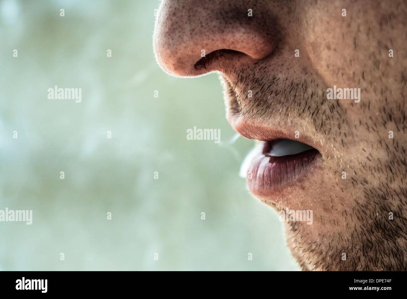 Detail of smoker male face smoking - Stock Image