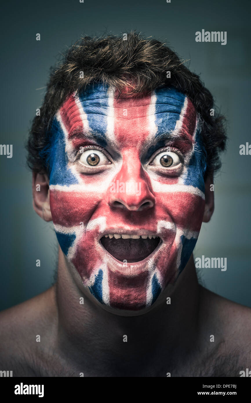 Portrait of shocked man with British flag painted on face. - Stock Image