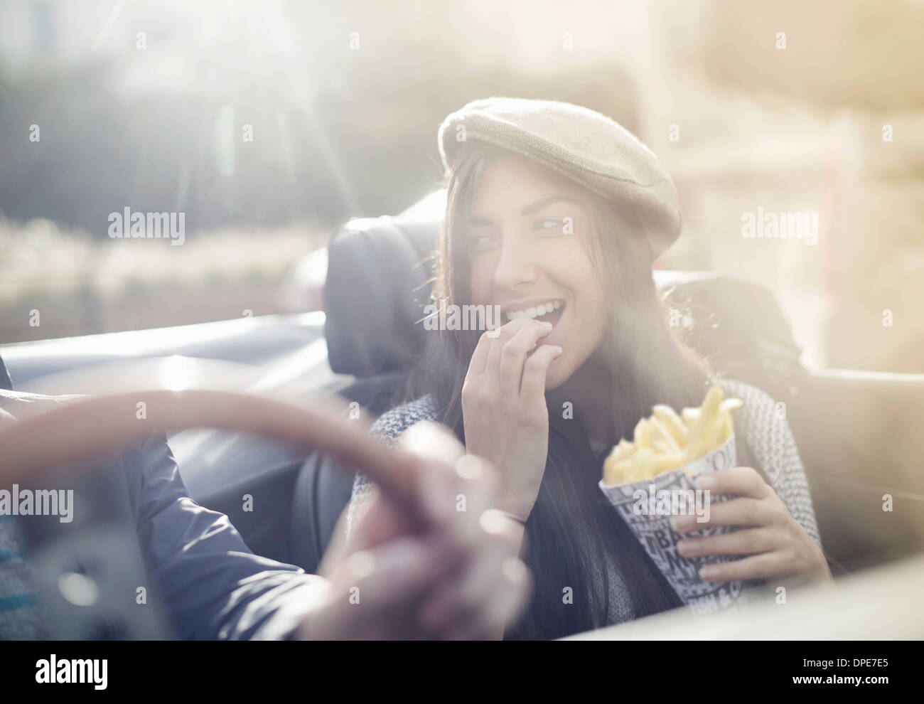 Young couple in convertible, woman eating chips - Stock Image