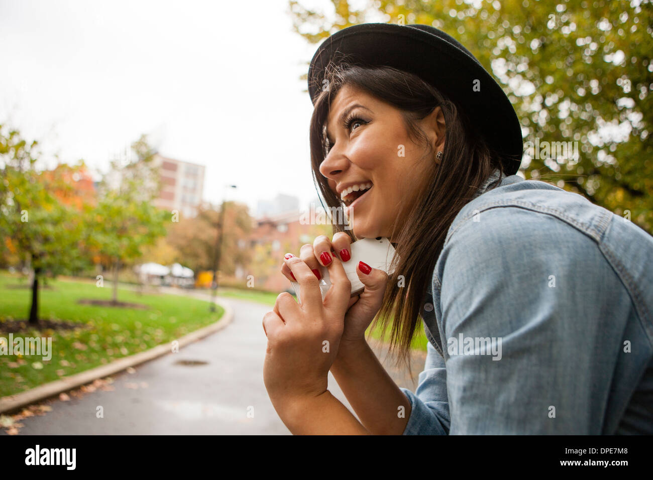 Woman holding cellular phone to chin - Stock Image