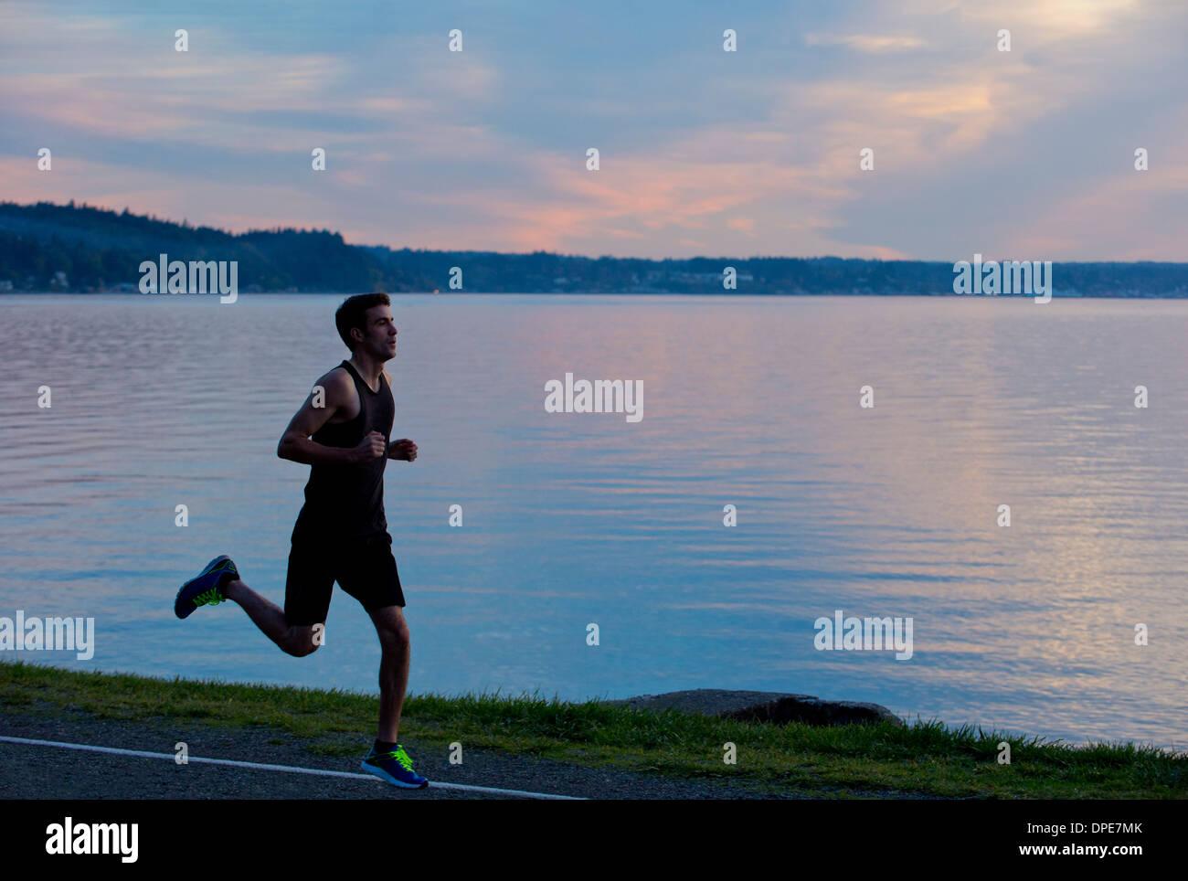 Jogger running past lake - Stock Image