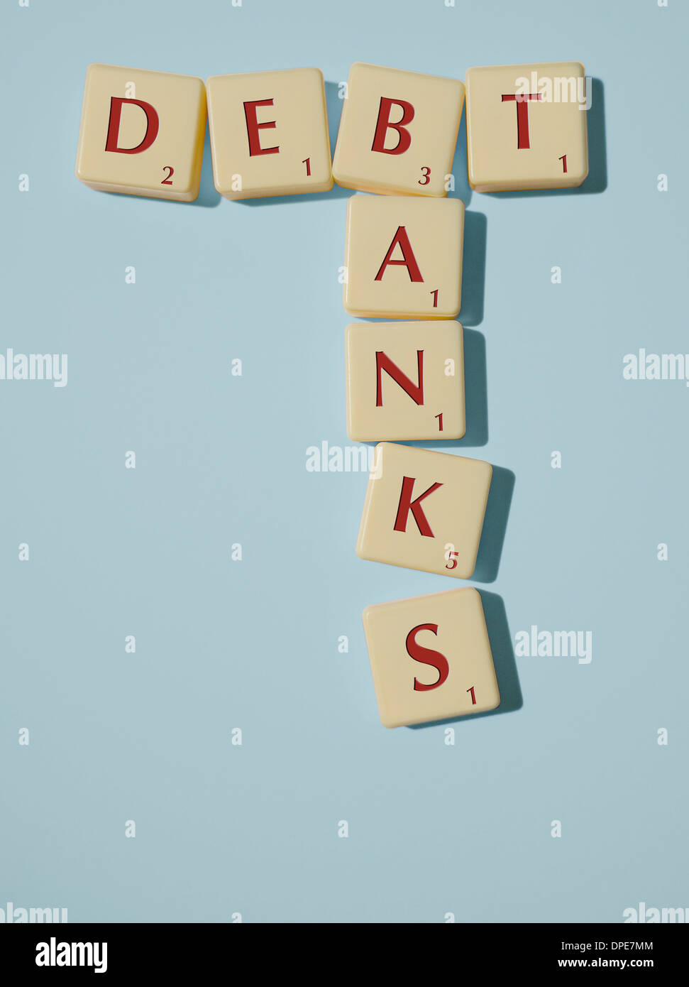 Scrabble Pieces arranged to spell out the words Debt and Banks on a Blue Background - Stock Image