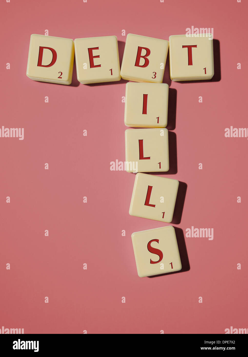 DEBT and BILLS spelled out in Scrabble Pieces on a pink background - Stock Image