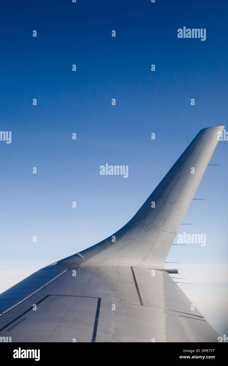 Vertical image of an airplane wing, taken from inside the airplane while flying. - Stock Image