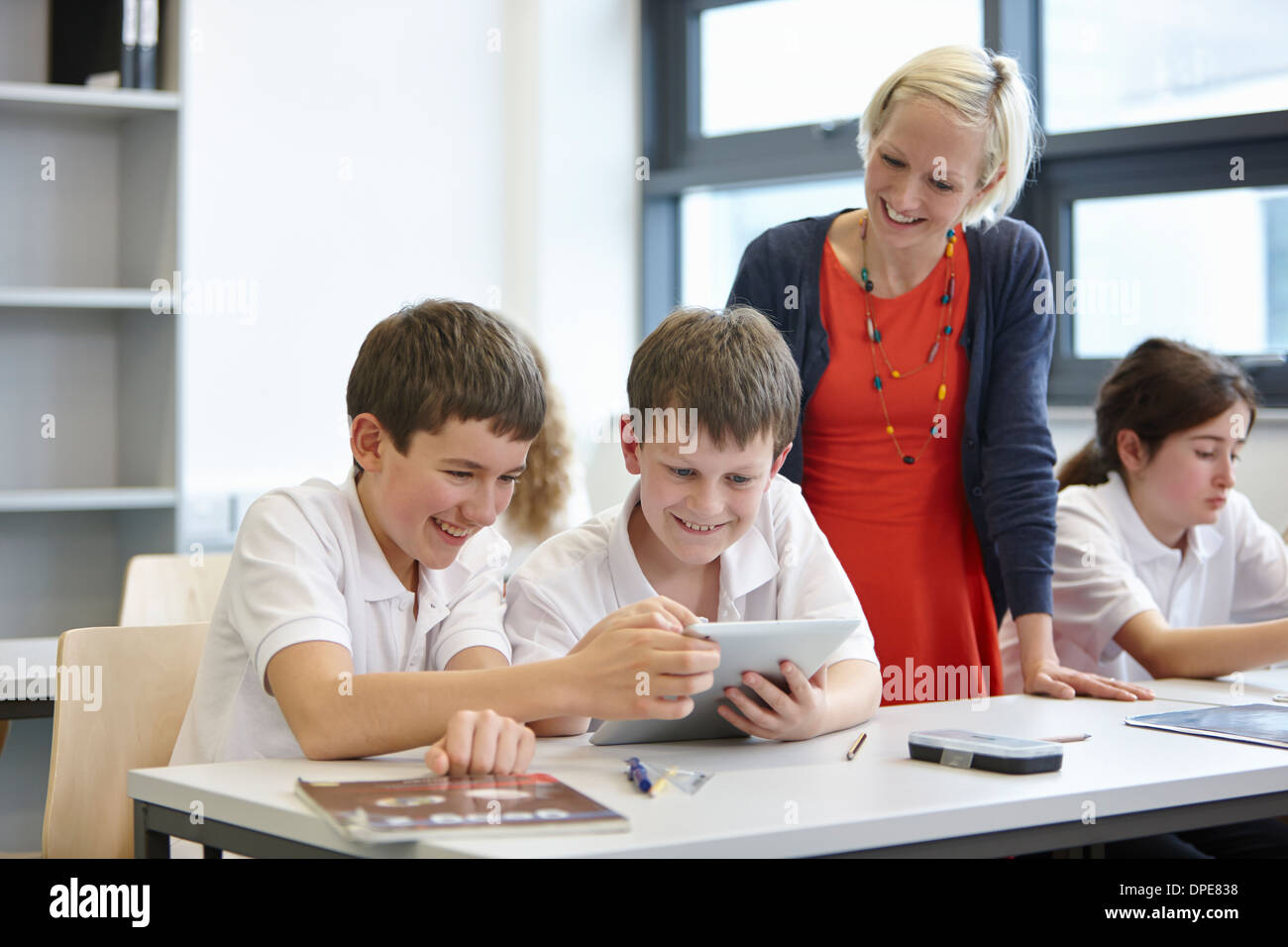 Schoolchildren working in class with teacher - Stock Image