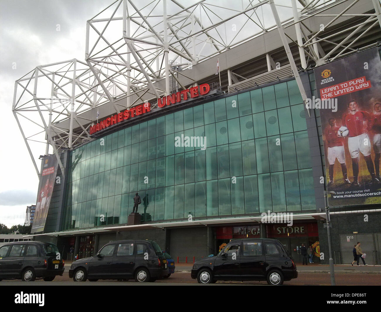 Old Trafford manchester united football club with taxi's waiting outside - Stock Image