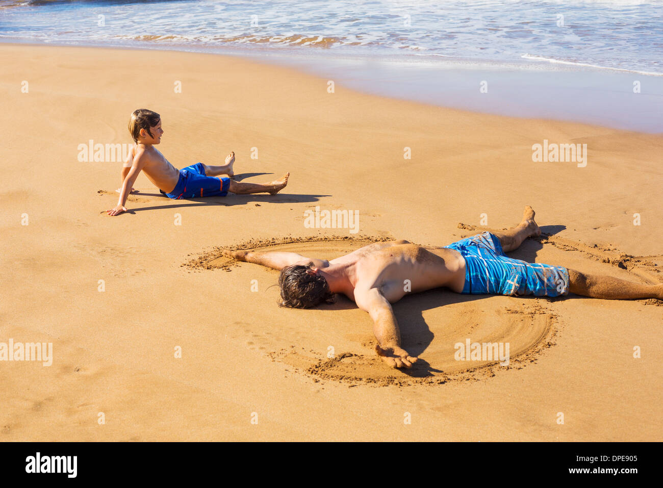 Father and son playing together in the sand on tropical beach on vacation - Stock Image