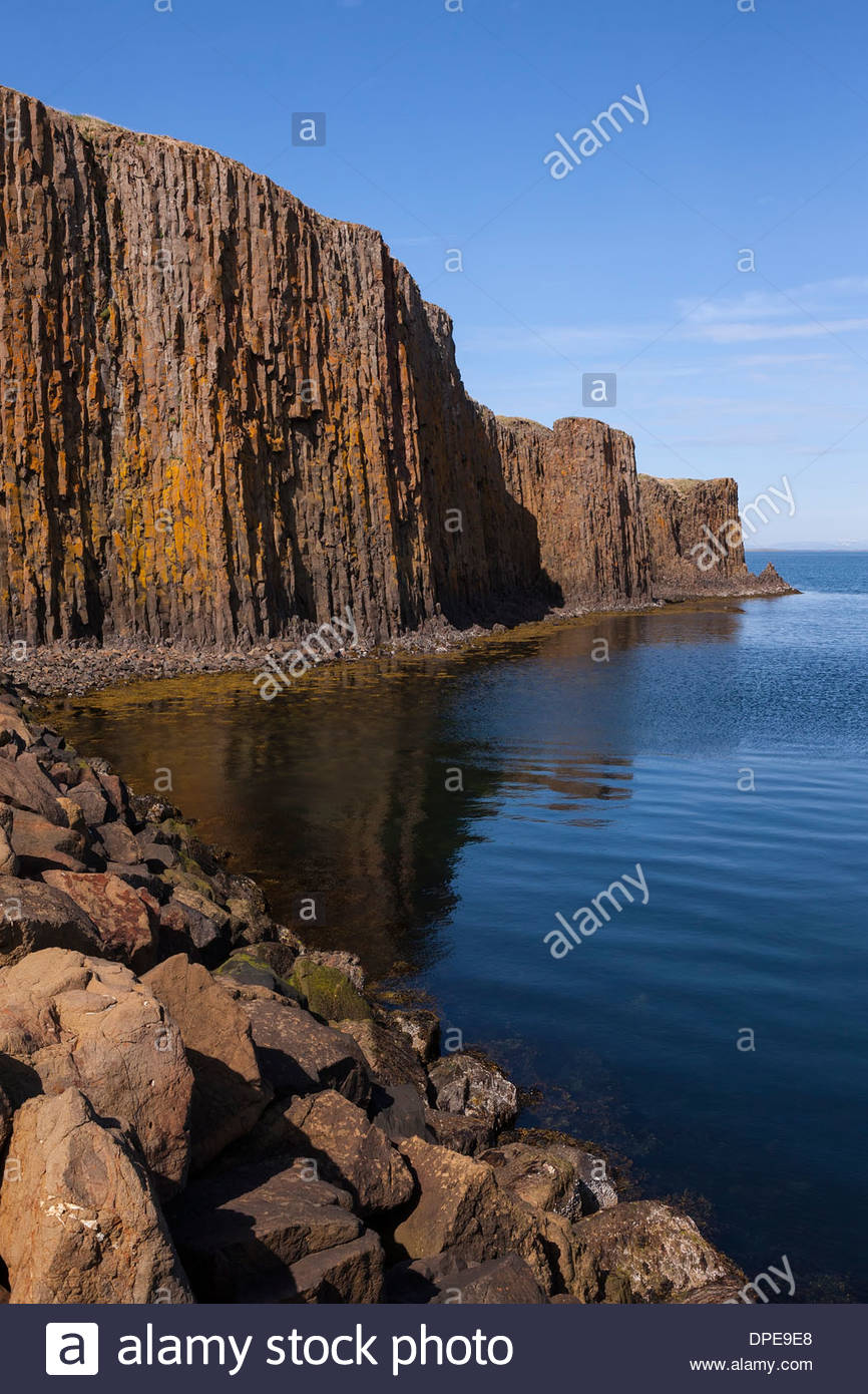 A towering columnar basalt cliff is partially reflected in the waters of Breiðasund in the town of Stykkishólmur, Iceland. - Stock Image