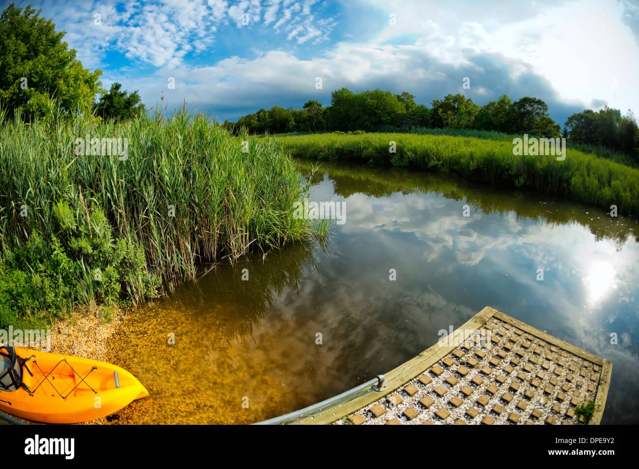 peaceful marshland stream with ramp, orange kayak, reflections of sky, a serene 180 degree fish eye landscape Long Island, NY US - Stock Image