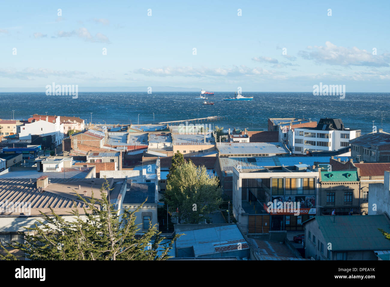 PUNTA ARENAS, Chile - A strong wind whips up whitecaps on the Strait of Magellan as seen over the rooftops of Punta Arenas, Chile. The city is the largest south of the 46th parallel south and capital city of Chile's southernmost region of Magallanes and Antartica Chilena. - Stock Image