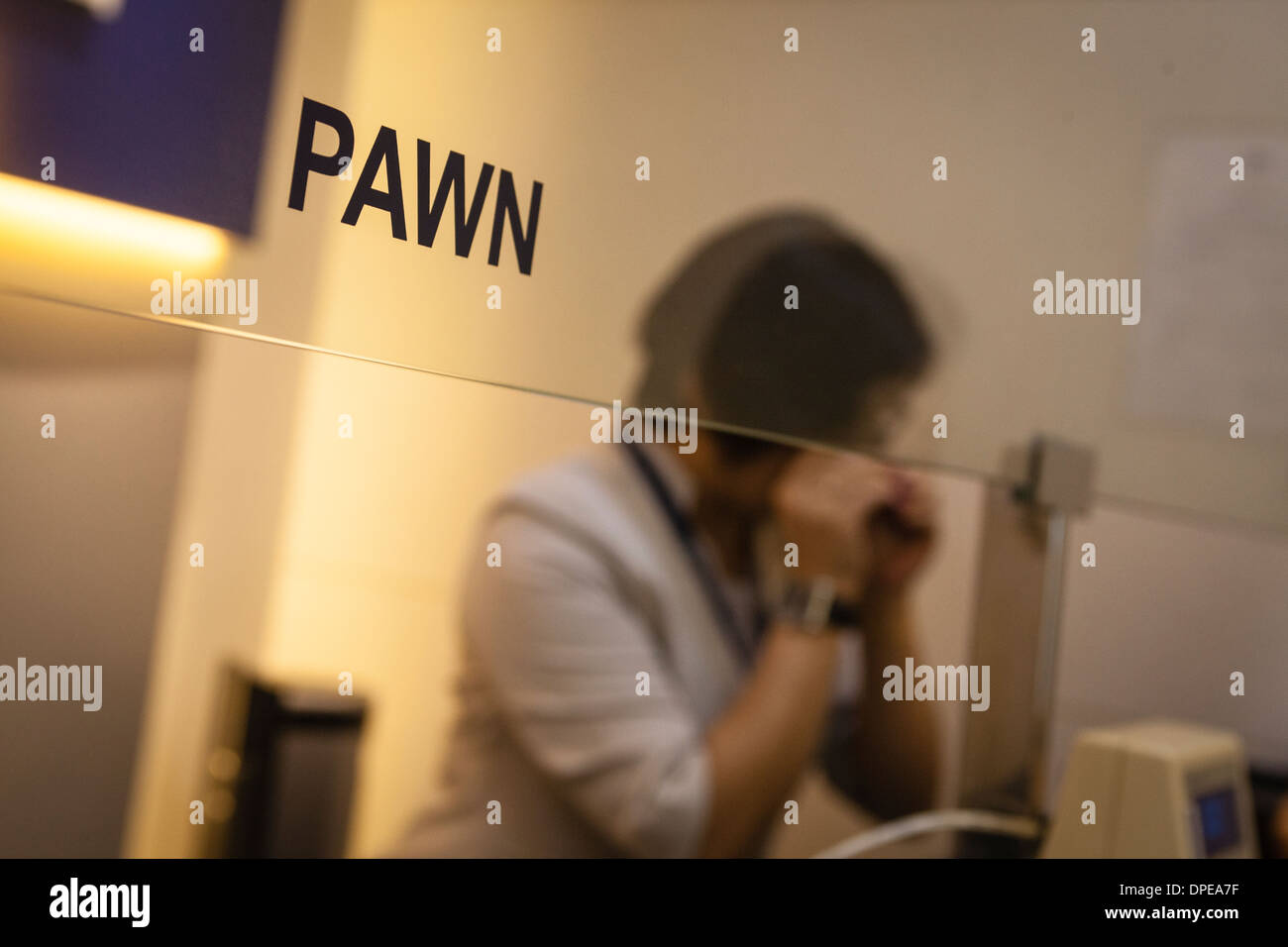 A salesperson evaluates a ring at a branch of Maxi-Cash pawnbrokerage in Singapore - Stock Image