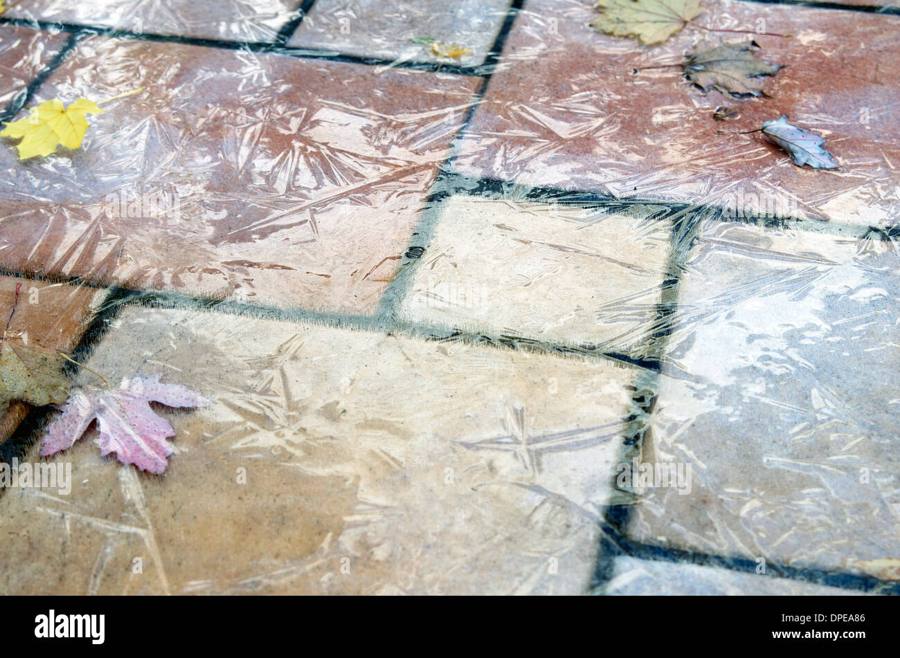 Icy surface outside on ceramic tile. Dangerous - Stock Image