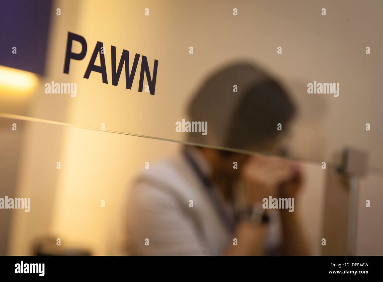 A salesperson examines a ring at a branch of Maxi-Cash pawnbrokerage in Singapore - Stock Image