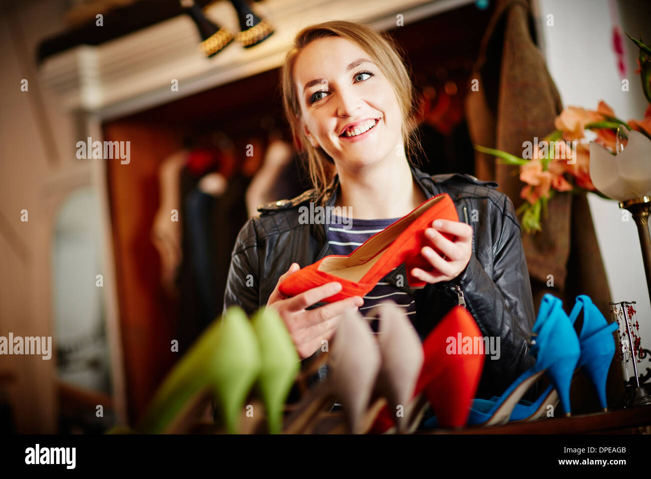 Young woman looking at selection of high heeled shoes - Stock Image