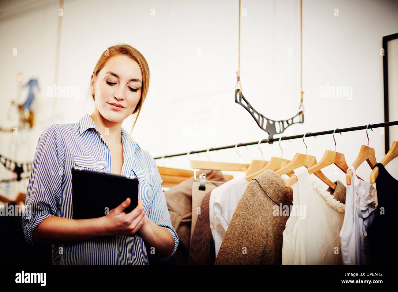 Shop keeper doing stock check using digital tablet - Stock Image
