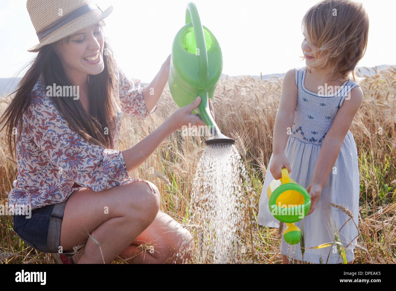 Mother and daughter in wheat field with watering cans - Stock Image