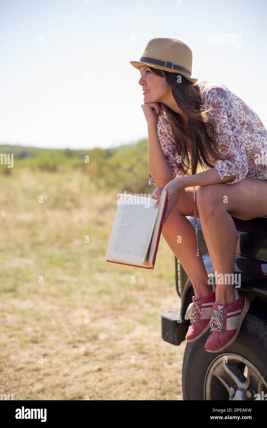 Mid adult women sitting on hood of car holding book with chin on hand - Stock Image