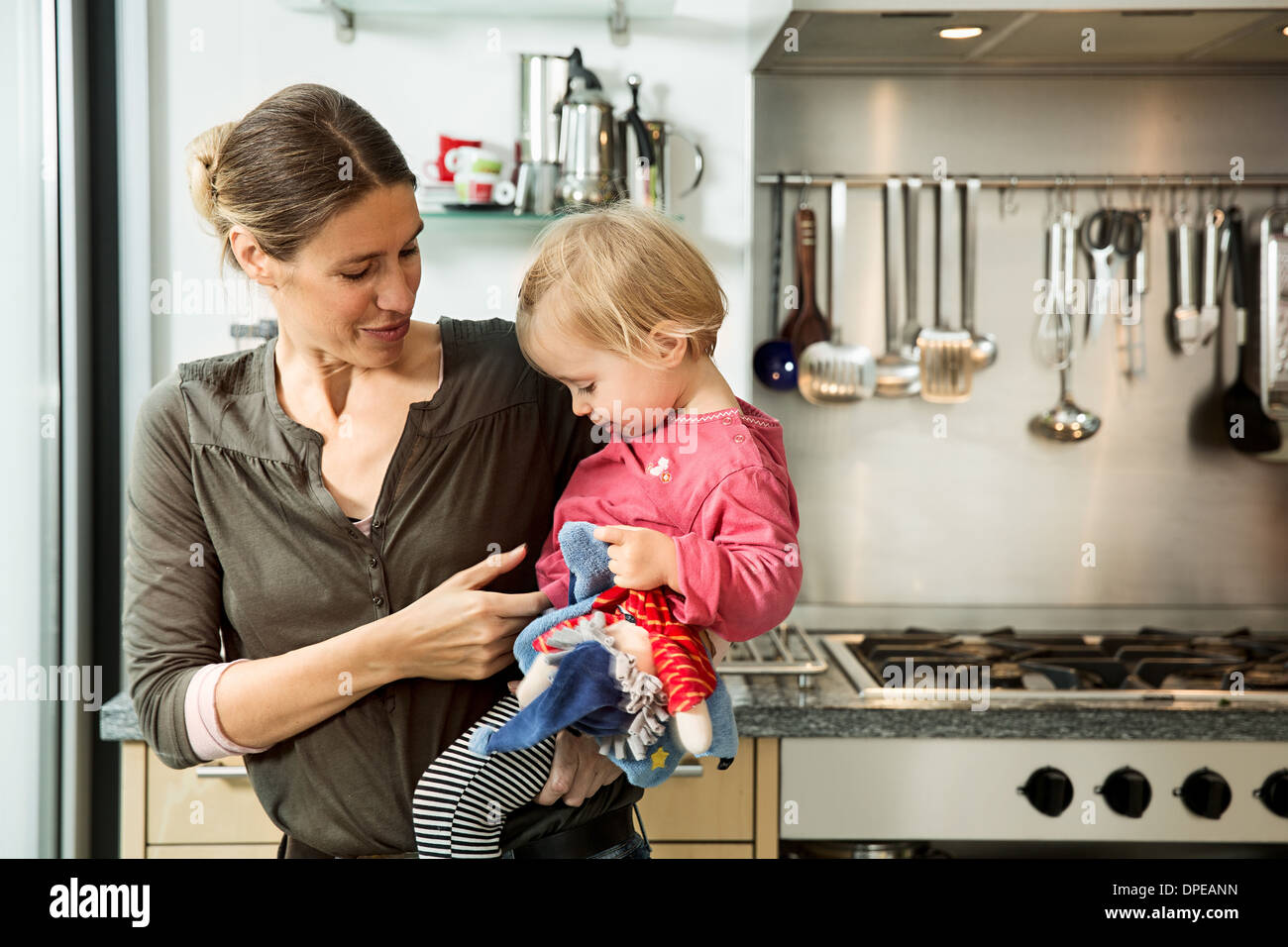 Mother carrying baby girl in kitchen Stock Photo