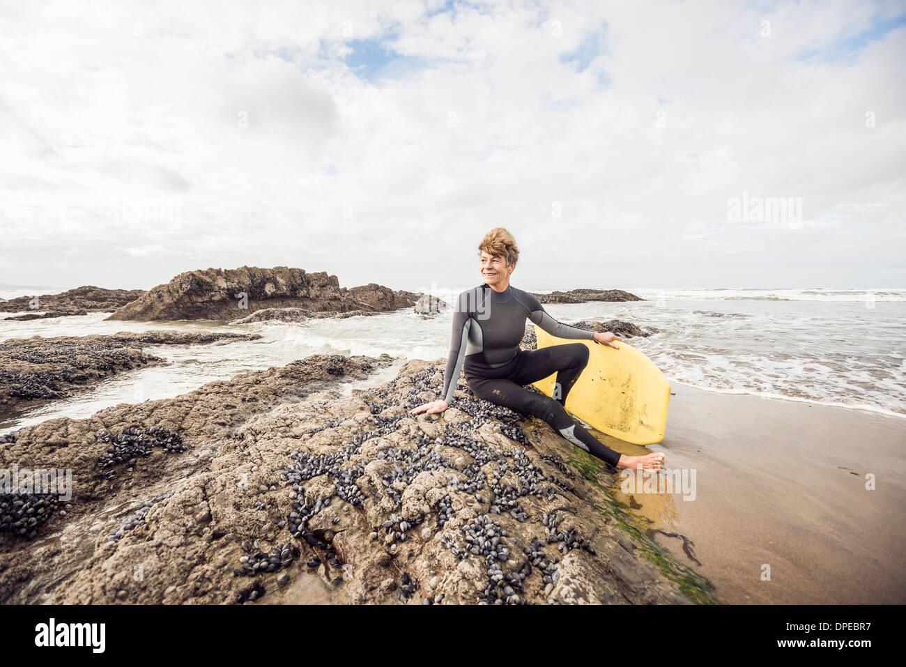 Mature female bodyboarder sitting on rocks, Devon, UK - Stock Image