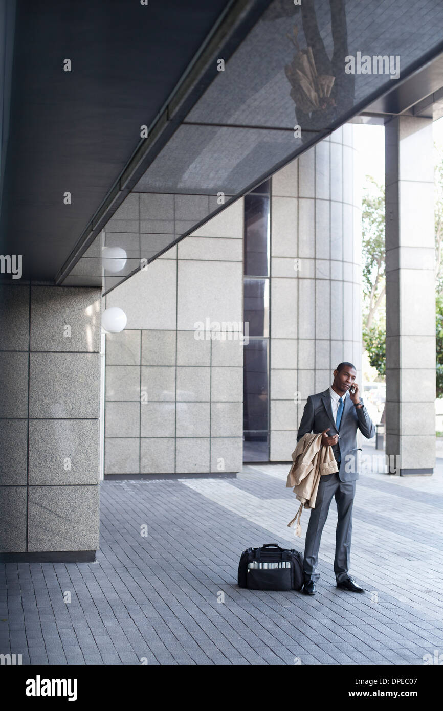 Businessman standing outside with bag and coat - Stock Image