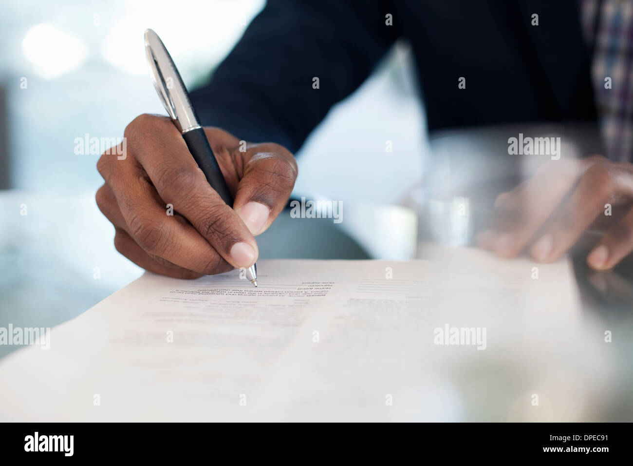 Cropped image of businessman signing paperwork - Stock Image