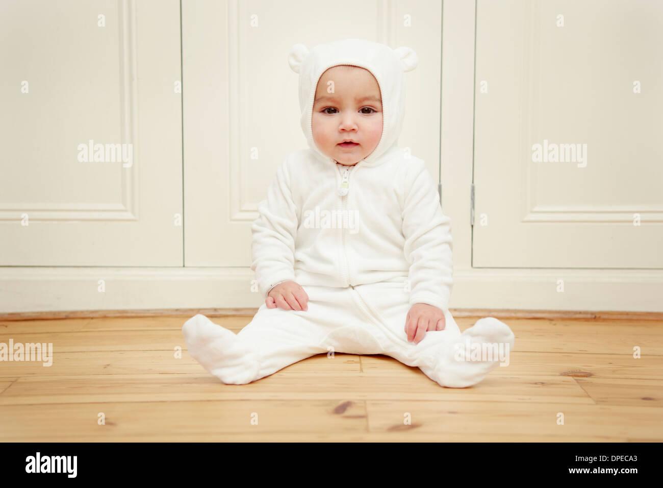 Baby sitting wearing bear babygro - Stock Image