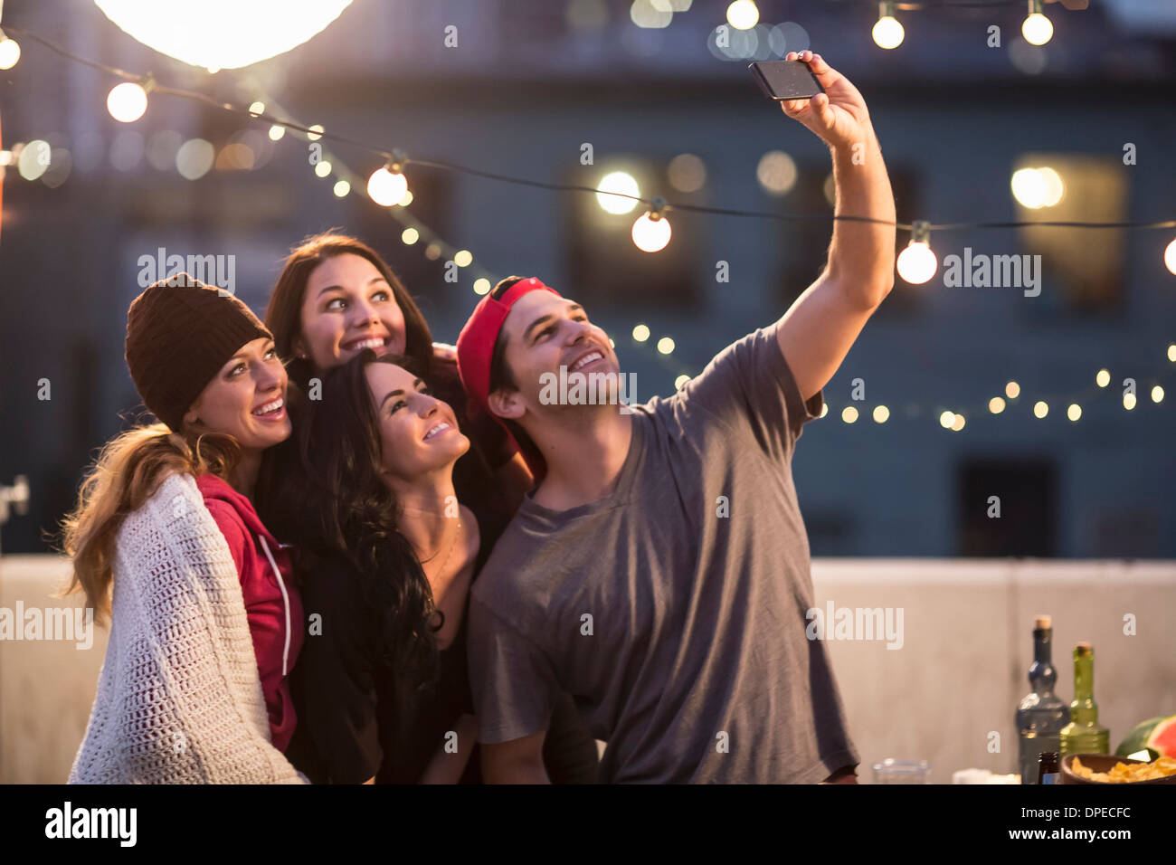 Young adult friends taking self portrait at party - Stock Image