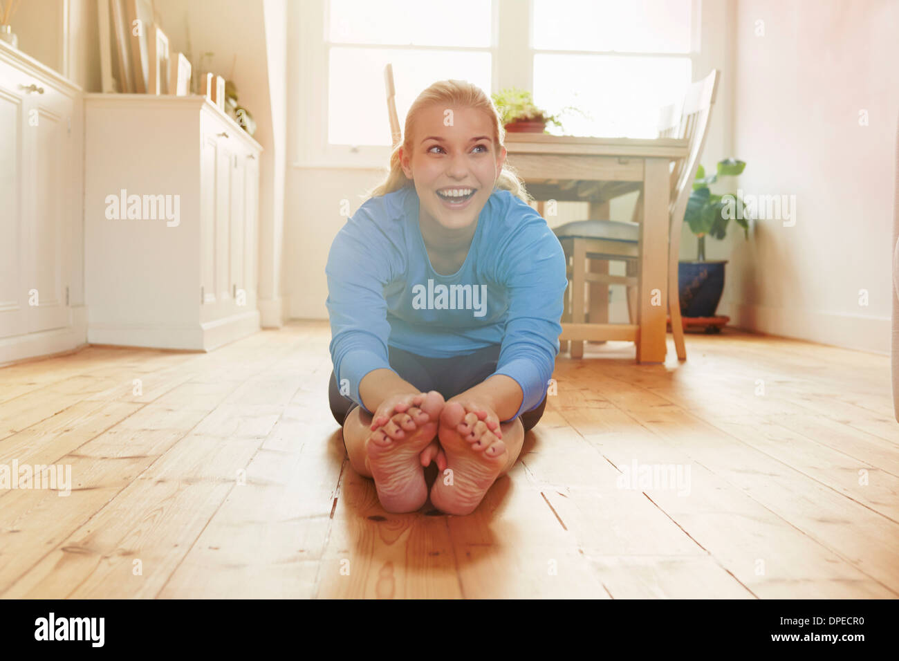 Young woman sitting on floor leaning forwards touching toes - Stock Image