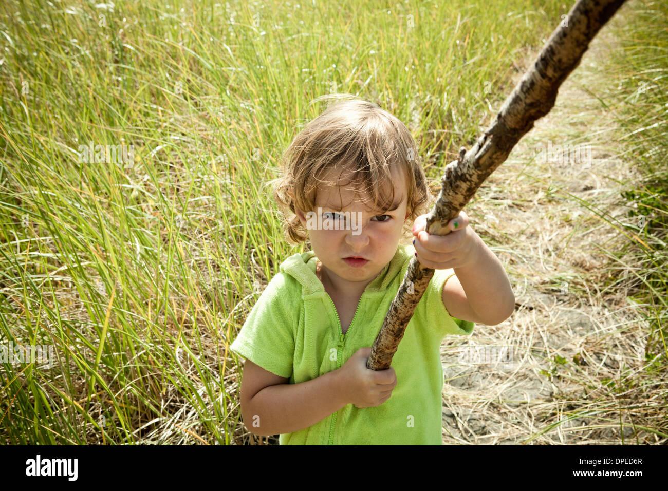 Portrait of female toddler holding long stick Stock Photo