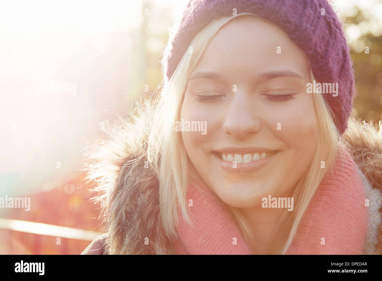 Portrait of young woman wearing knit hat, eyes closed - Stock Image
