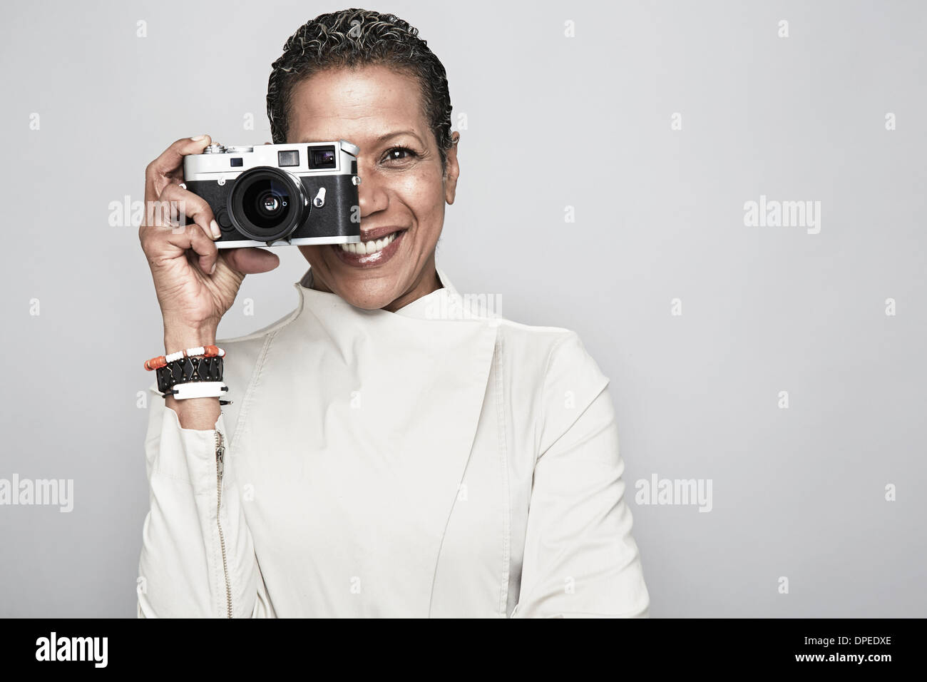 Studio portrait of happy mature woman holding up camera - Stock Image