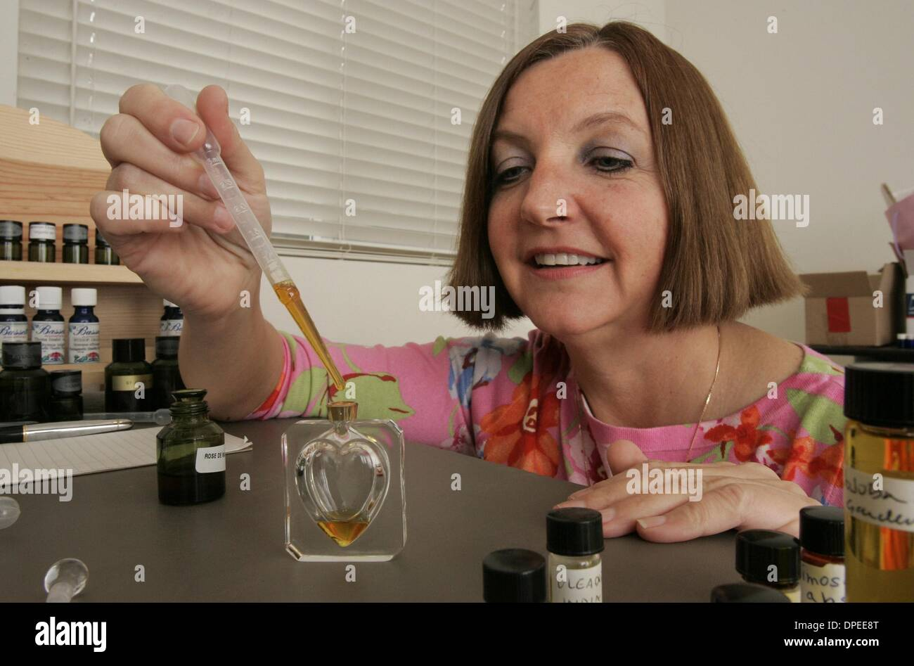 (Published 2/20/2005, N-6)  JoANNE BASSETT places drops of rose de mai, made from May roses in France, into a bottle for some special perfume she's making.  U/T photo CHARLIE NEUMAN - Stock Image