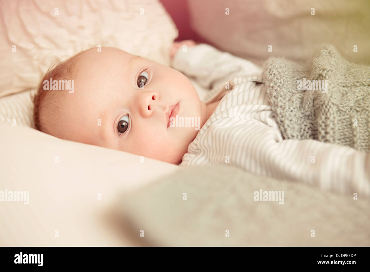 Two month old baby boy lying awake in crib - Stock Image