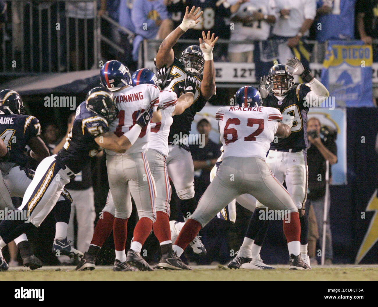 (Published 9/27/2005, Signon)  9/25/2005.Giants QB Eli Manning throws a touchdown pass to Plaxico Burress while Chargers linebacker Ben Leber (left) is called for roughing the passer.UT/DON KOHLBAUER - Stock Image