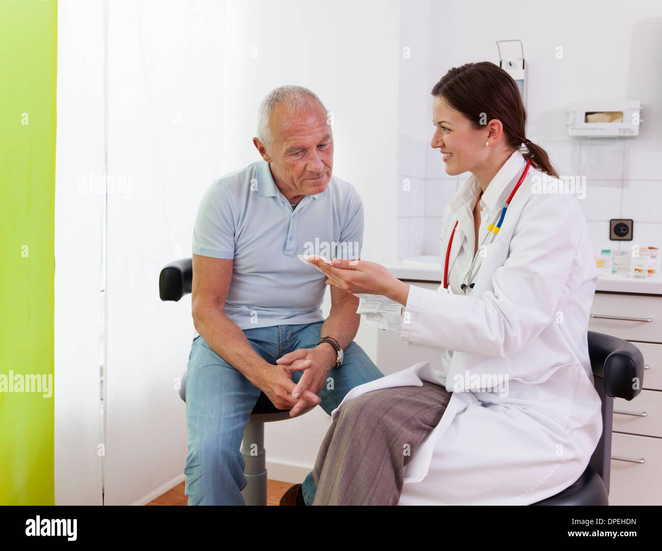 Female doctor talking to senior male patient - Stock Image