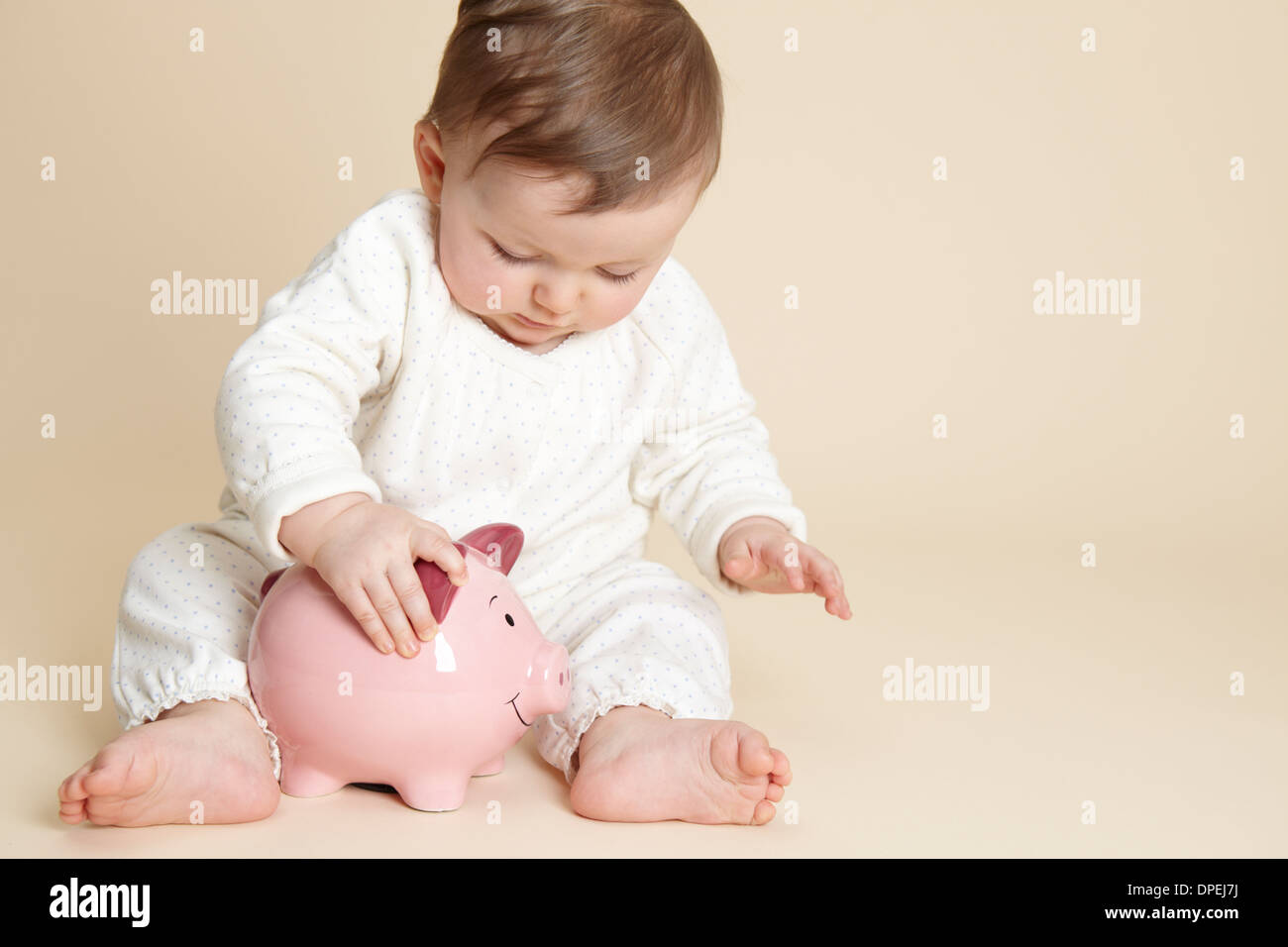 Studio portrait of baby girl playing with piggy bank - Stock Image